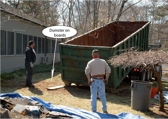Step 8 - Dumpster - having it close to the roof. Make sure you get a big enough dumpster to remove all the roofing debris. Always put boards down for the dumpster to stand on to protect the surface.