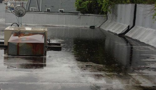 Ponding water due to a blocked drain. The water pooling is adding a lot of stress to the flat roof.