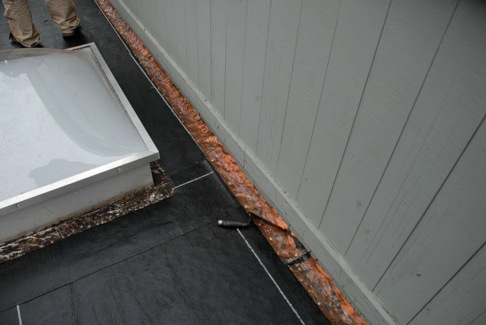 Copper flashing on an old flat roof to be re-used