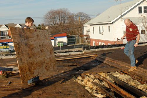 Erik helps repair a flat roof.