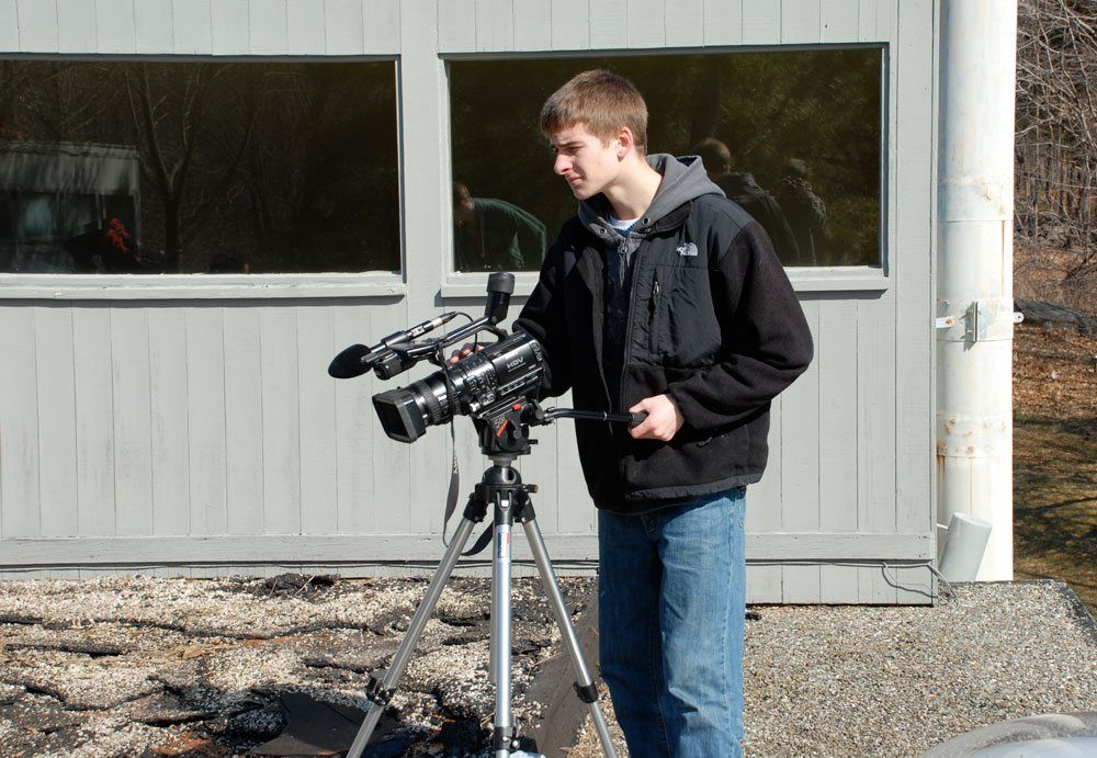 Erik on the camera taking video footage of a flat roof