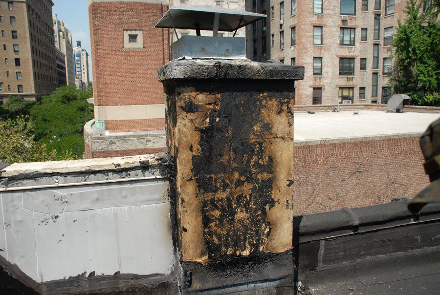 Flat Roof Chimneys and Flashing - This chimney had been continually smeared with tar but the leaking continued.